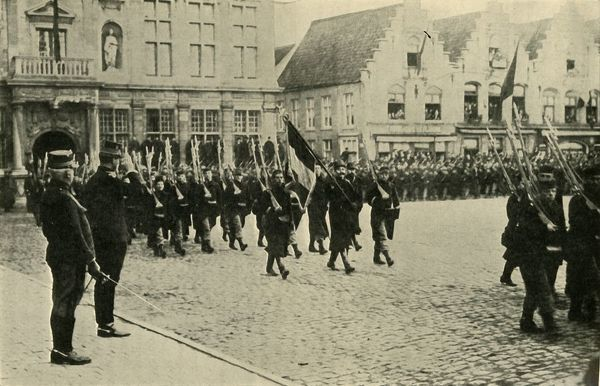 "Albert I of Belgium reviewing troops, First World War, 1914, (c1920). 'Heroes of the Belgian Army: the 75th Regiment marching past King Albert with their colours decorated with the Royal Albert Order'. From ""The Great World War - A History"" Volume I"