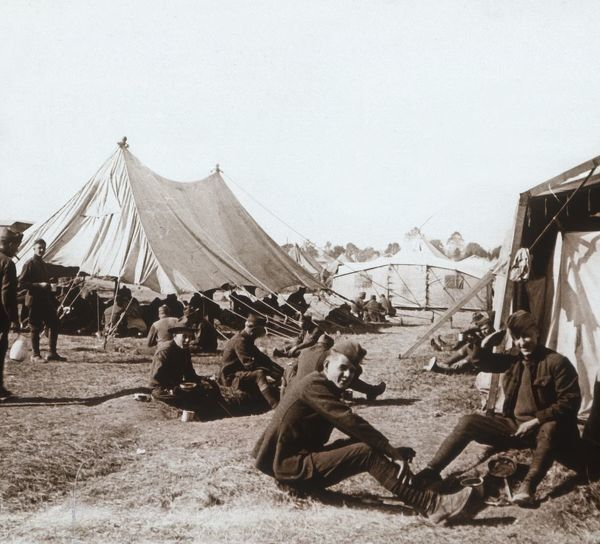 American camp, Melette, France, c1914-c1918. Soldiers sitting on the ground, one saluting. Photograph from a series of glass plate stereoview images depicting scenes from World War I (1914-1918)