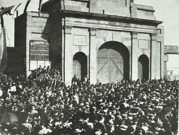 Crowd outside the closed East India Dock Gates, Poplar, London, 1897. Men wait, locked out of the East India Docks, probably during a strike in which the dock workers demanded fair pay and conditions. The most famous docker's strike took place in 1889