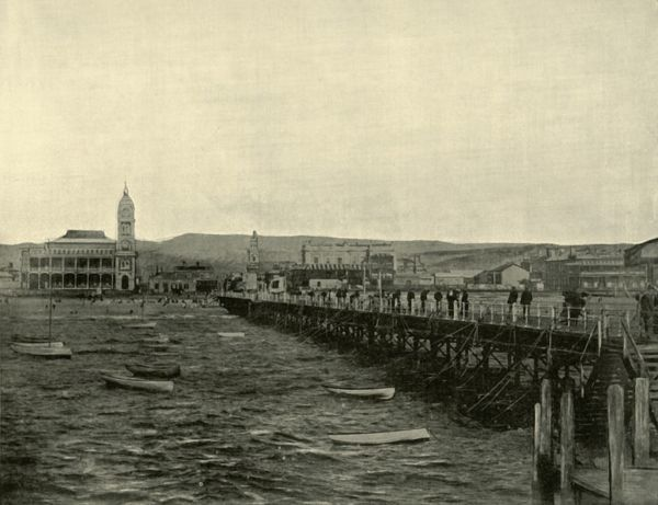'Glenelg', 1901. Glenelg, a suburb of Adelaide on Holdfast Bay in Gulf St Vincent, established 1836, the oldest European settlement on mainland South Australia, prior to which it was home to the Kaurna Indigenous Australians. The jetty was built in 1857