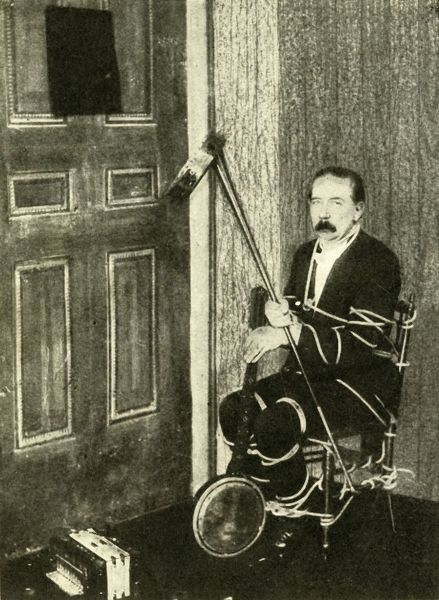 "John Nevil Maskelyne performs a 'spirit cabinet illusion', c1910. 'How the tricks are performed - ""A coach-horn or megaphone is useful for picking things up and putting them through the aperture in the door when securely tied'&quot"