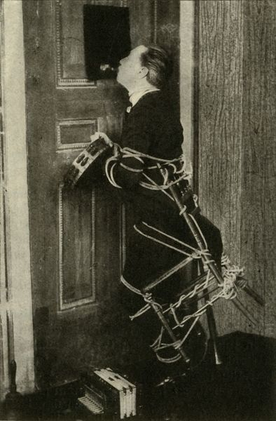 John Nevil Maskelyne performs a 'spirit cabinet illusion', c1910