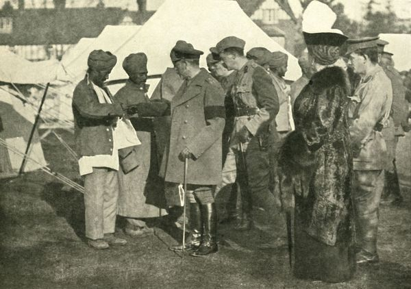 King George and Queen Mary visit wounded soldiers, First World War, 1915, (c1920). 'Wounded Heroes from the Front: Their Majesties visiting one of the Indian Hospital Camps'. The British king and queen talking to Indian soldiers at a field hospital