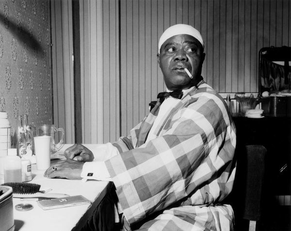 Louis Armstrong relaxing backstage, Finsbury Park Astoria, London, 1962