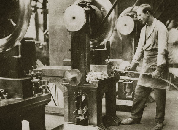 Money making; cutting strips of silver into disks, 20th century. The cutting machine stamps out a double row of disks