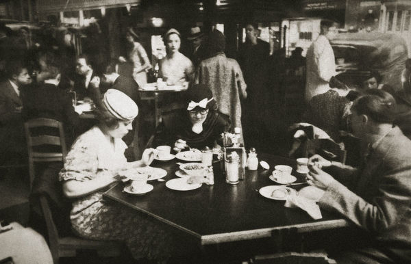 Office workers lunching in a restaurant, New York, USA, early 1930s. The reflection of car can be seen in the window