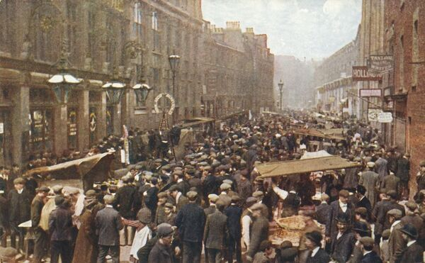 Petticoat Lane market on a Sunday morning, London, c1910. Crowds at the street market in Spitalfields. Postcard. [Celesque Series, Photochrom Co Ltd]