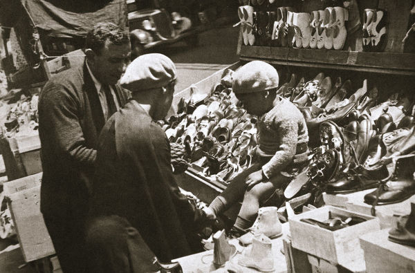 A woman from Harlem buys a pair of shoes for her child, New York, USA, c1920s-c1930s