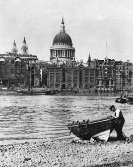 Thames waterman and his boat on the 'beach' at Bankside, London, 1926-1927